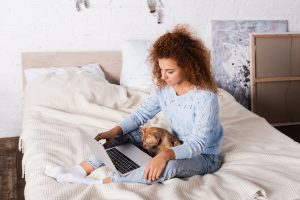 Young Red Haired Woman Looking At Laptop Near Cat In Bedroom doing online therapy in Chicago, IL with her online therapist in Illinois. She get support with women's counseling for anxiety, depression and more at Flourish Counseling and Wellness in the Chicago Loop 60604, 60605, 60607.