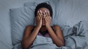 A photo of a Black woman in bed with her hands covering her face. She is feeling stressed out about starting counseling in Chicago. She is considering starting online therapy in Chicago to help with scheduling conflicts. | 60605 | 60607 | 60305 | 60130