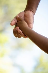 A photo of a mom's hand holding her baby's hand. She is feeling connected to her child after working with a postpartum depression counselor in Chicago. She worked with a counselor at Flourish Counseling and Wellness. | 60301 | 60302 | 60305