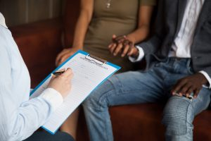 Image of a couple holding hands while sitting on a couch across from a professional. This image illustrates what a couple looking into third party reproduction in Chicago, IL may look like. You can work with a PMH-C in Chicago, IL if you'd like to build a family. | 60604 | 60605 | 60607
