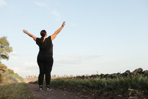 Image of a woman on a trail run standing with her arms stretched above her. This image represents the relief one can feel from anxiety symptoms after working with an anxiety therapist in Chicago, IL. | 60604 | 60605 | 60607