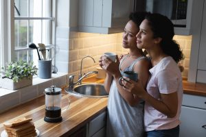 Image of two women standing together in an embrace in the kitchen while looking out a window. This image illustrates how helpful a couples therapist in Chicago, IL can be to partners. Check out marriage counseling in Chicago, IL to learn about the benefits of couples therapy.   60604   60605   60607